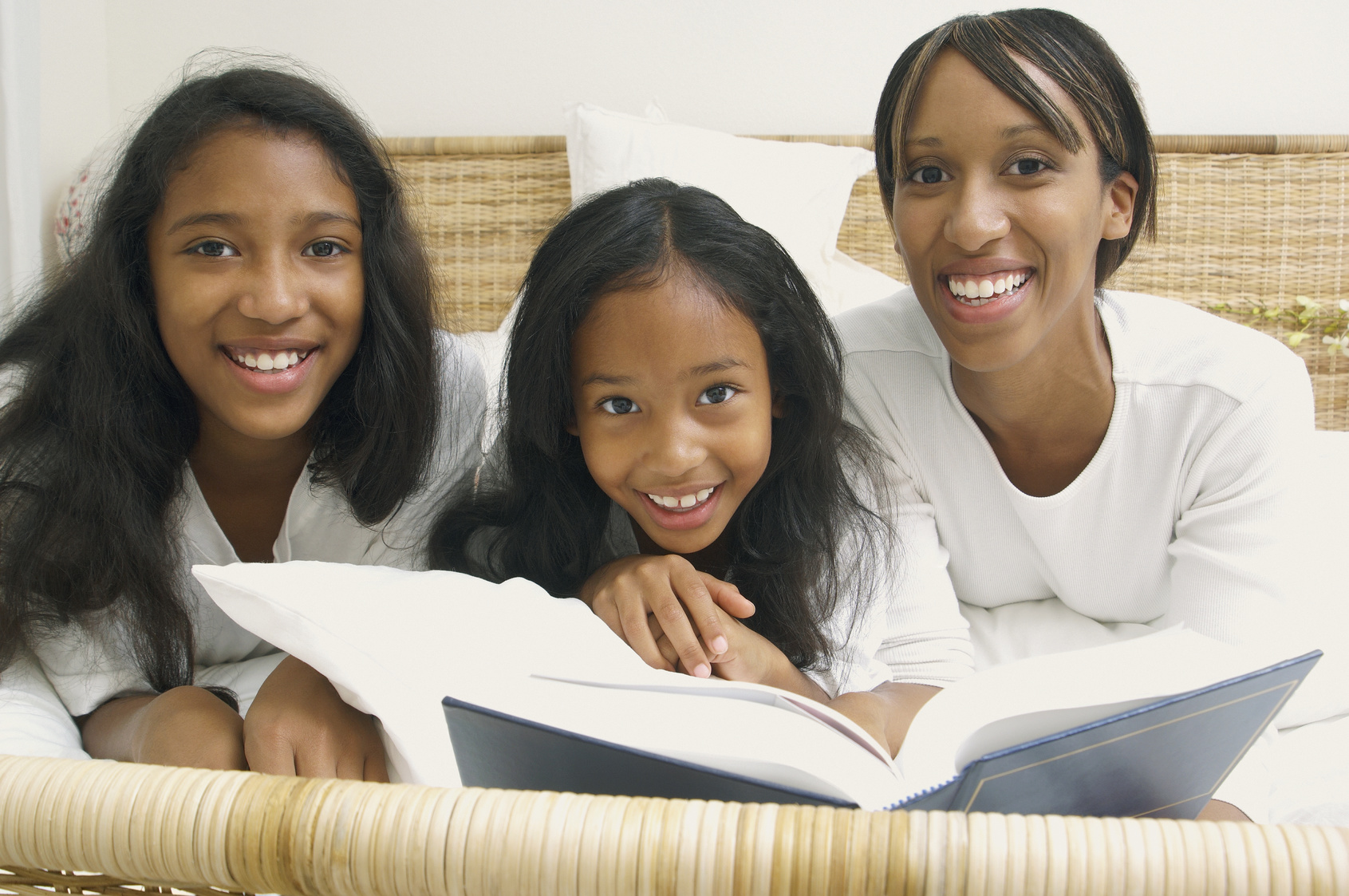 African American mother and daughters on bed with book