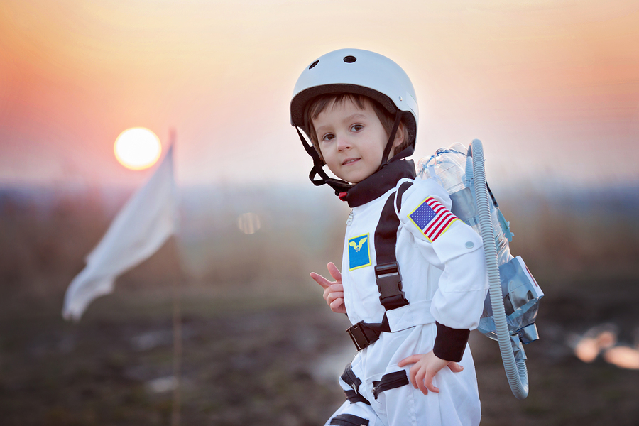 Adorable little boy dressed as astronaut playing in the park with rocket and flag dreaming about becoming an astronaut
